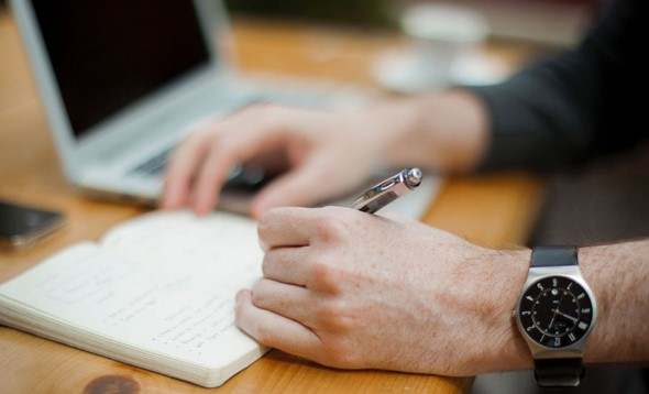 Male hands taking notes in notebook on a desk with laptop open, only hand, pen and wristwatch in focus