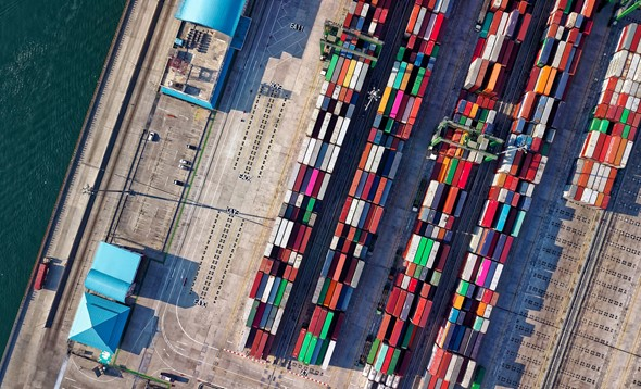 Overhead aerial shot of several stacks of multi-coloured containers stored on a dock