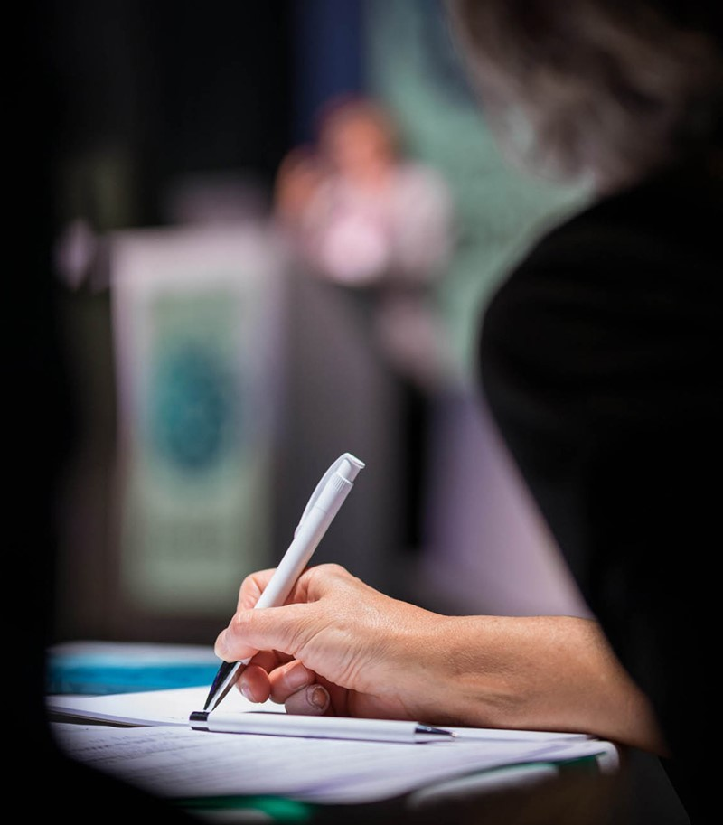 Woman's hand taking notes with white pen during a speech, only hand and pen in focus, rest of picture blurry