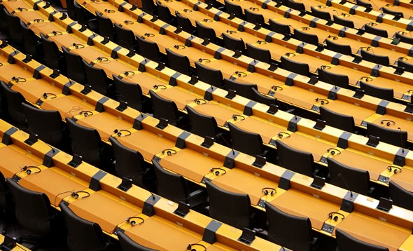 Rows of empty seats from a parliament hemicycle with headphones on desks and electronic voting equipment fitted