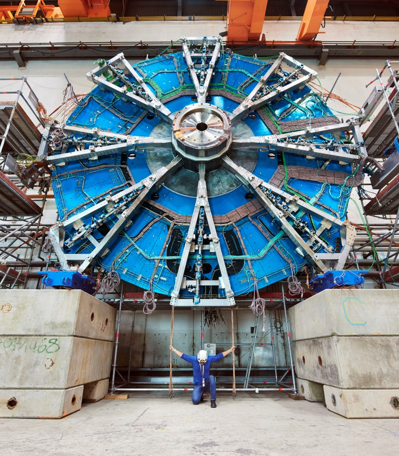 Man in protective gear for building sites kneeling before viewer under a large piece of equipment from CERN