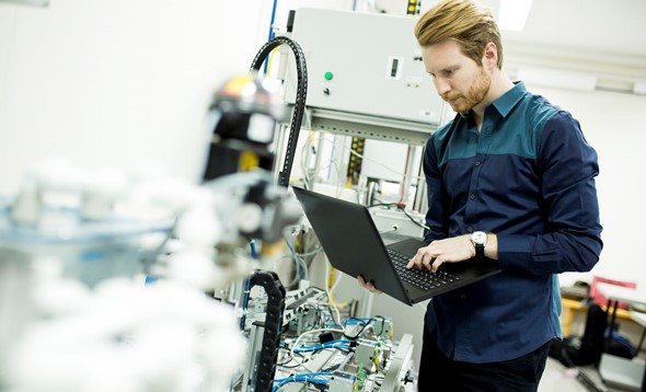 Man with laptop in hand examining complex piece of machinery