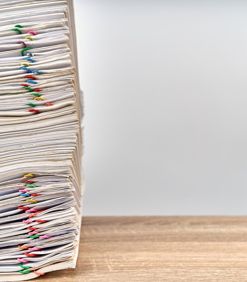 Large stack of files with multicoloured paperclips attached on a wooden desk, stack aligned to the left of the picture
